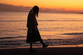 水の体の上に日没の前に立っている人の写真・画像素材[967740]
