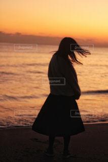 水の体の上に日没の前に立っている女性の写真・画像素材[967743]