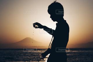 日没の前に立っている男の写真・画像素材[1287591]