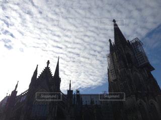 建物の側に時計と大きな背の高い塔の写真・画像素材[792177]