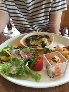 食品のプレートをテーブルに座っている女性 - No.1147114
