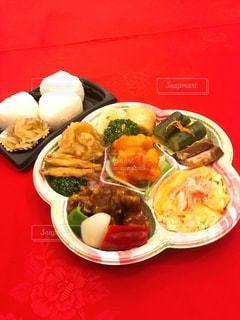 赤いトレイの上に食べ物のプレートの写真・画像素材[1641348]