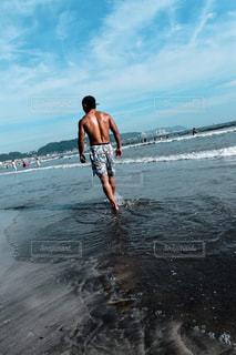 水の体の近くのビーチに立っている人 - No.720560