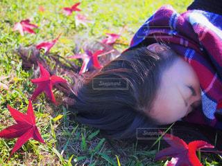 赤いジャケットを着ている人は草の上に座っています。の写真・画像素材[1699318]