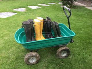 緑の芝生の上にカートと長靴 - No.747835
