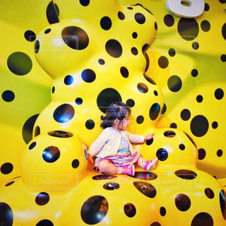 黄色と黒の大きな椅子に座る女の子の写真・画像素材[810028]