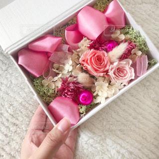 女性,花,ピンク,白,フラワーアレンジメント,フラワー,手,バラ,プレゼント,薔薇,リボン,贈り物,フラワーアレンジ,プリザーブドフラワー,フラワーボックス,片手,フラワーギフト