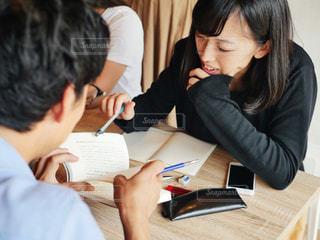 ノート パソコンを見てテーブルに座っている女性の写真・画像素材[1318987]
