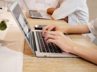 テーブルの上に座っているラップトップ コンピューターを使用している人の写真・画像素材[1525442]