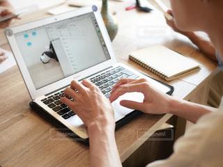 木製テーブルの上に座っているラップトップ コンピューターを使用している人の写真・画像素材[1544310]