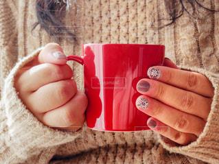 赤のカップを持っている手の写真・画像素材[1748970]