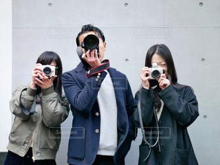 立っていると、電話で話している人々 のグループの写真・画像素材[1829393]