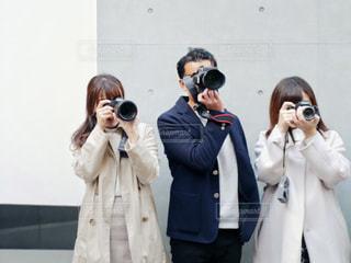 立っていると、電話で話している人々 のグループの写真・画像素材[1829397]