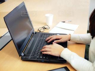 テーブルの上に座っているラップトップコンピュータを使用している人の写真・画像素材[2310061]