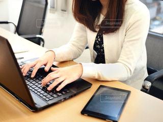 ラップトップコンピュータを使ってテーブルに座っている女性の写真・画像素材[2311328]