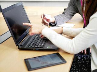 ラップトップコンピュータを使ってテーブルに座っている女性の写真・画像素材[2312272]