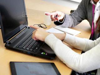 テーブルの上に座っているラップトップコンピュータを使用している人の写真・画像素材[2312273]