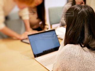 ラップトップコンピュータを使ってテーブルに座っている女性の写真・画像素材[2406376]