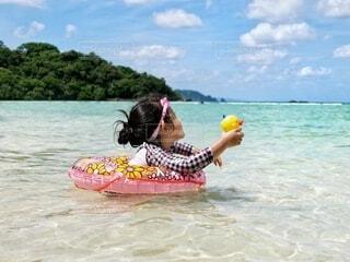 透明な海でおもちゃと浮き輪で水遊びする女の子の写真・画像素材[4681243]