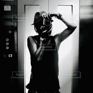 鏡の前に立ってカメラのポーズをとる人の写真・画像素材[3927878]