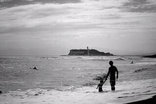 海の隣のビーチを歩いている男の写真・画像素材[4512660]