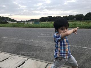 草の中に立っている小さな男の子の写真・画像素材[705859]
