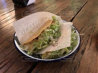 サンドイッチと木製のテーブルのサラダ プレートの写真・画像素材[922543]