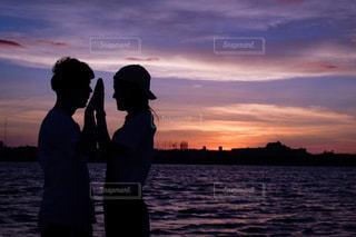 夕日,カップル,夕陽,手を合わせる,ジェスチャー,気持ちが合わさった瞬間