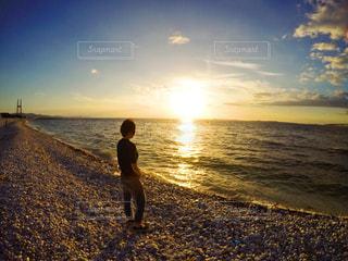 水の体の近くのビーチに立っている人の写真・画像素材[1226747]