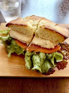 半分に切って、テーブルの上に座ってサンドイッチ - No.738397