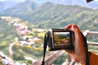 背景の山を持っている手の写真・画像素材[1014310]