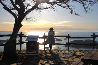 水の体の横にあるベンチに座っている人の写真・画像素材[1015635]
