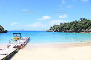 水の体の近くのビーチにボートの写真・画像素材[1107358]