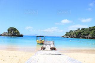 水の体の近くのビーチに座ってボートの写真・画像素材[1107366]