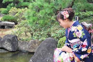 岩の上に座っている少女の写真・画像素材[1717528]