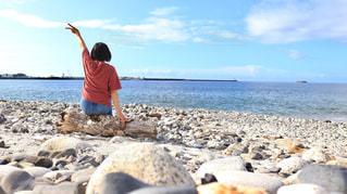 水域の隣の岩のビーチに立っている男の写真・画像素材[2129800]