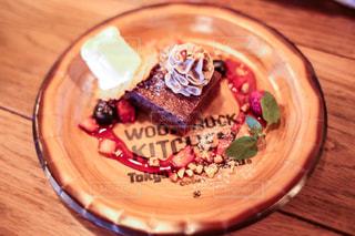 木製テーブルの上の皿にケーキの写真・画像素材[811877]