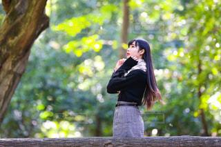 木の隣に立っている女性の写真・画像素材[1616727]
