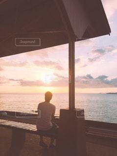 夕日に沈む秘境駅のベンチに座る男性の写真・画像素材[813137]