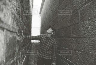 れんが造りの壁の横に立っている人 - No.848302