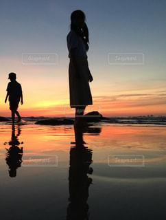 バック グラウンドで夕焼けのビーチに立っている人の写真・画像素材[826246]
