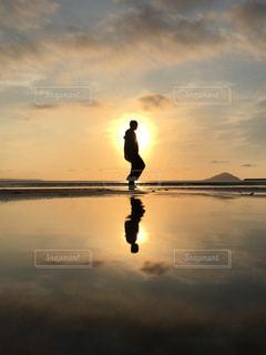 女性,海,空,夕日,太陽,ビーチ,夕暮れ,水面,反射,シルエット,光,リフレクション