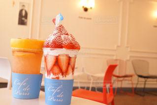 コーヒー カップの横にあるオレンジ ジュースのガラスの写真・画像素材[876994]