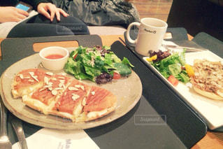 食品のプレートをテーブルに座っている女性の写真・画像素材[877496]