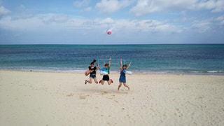 砂浜の上に空気を通って飛んで男の写真・画像素材[896686]