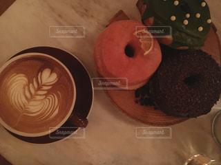 近くのコーヒー カップの横に座っているドーナツのアップ - No.1049979