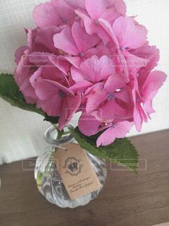 テーブルの上のピンクの花で一杯の花瓶の写真・画像素材[1249693]