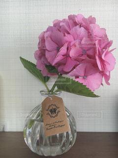 テーブルの上のピンクの花で一杯の花瓶 - No.1249694
