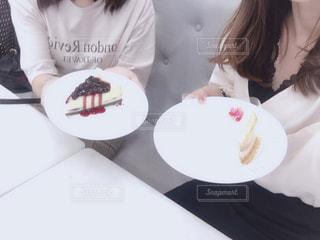 皿の上のケーキをテーブルに座っている女性の写真・画像素材[1490770]