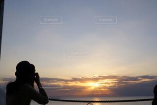 バック グラウンドで夕日を持つ人の写真・画像素材[1862268]